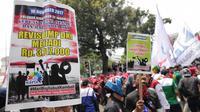 Massa buruh membawa spanduk berisi tuntutan dalam unjuk rasa di depan Balai Kota DKI Jakarta, Jumat (10/11). Bertepatan Hari Pahlawan, buruh dari berbagai daerah melakukan aksi turun ke jalan menuntut pengupahan yang layak. (Liputan6.com/Faizal Fanani)