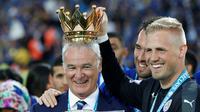 Kiper Leicester City, Kasper Schmeichel, bercanda dengan memasang mahkota trofi Liga Inggris di kepala Claudio Ranieri di Stadion King Power, Leicester, Sabtu (7/5/2016). (AFP/Adrian Dennis)
