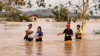 Warga mengarungi jalan raya yang banjir terjangan topan Phanfone di Ormoc City, Provinsi Leyte, Filipina, Rabu (25/12/2019). Topan membuat jutaan warga di negara yang mayoritas beragama Katolik itu merayakan Natal dengan kesedihan. (RONALD FRANK DEJON/AFP)