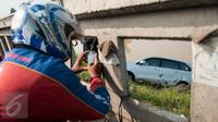 Seorang warga mengambil gambar mobil yang terperosok di saluran Ispeksi Kalimalang, Jabar, Minggu (7/5). Penyebab kecelakaan itu diduga pengemudi mengantuk dan menghindari pengendara motor sehingga tercebur kedalam Kalimalang.(Liputan6.com/Gempur M Surya)