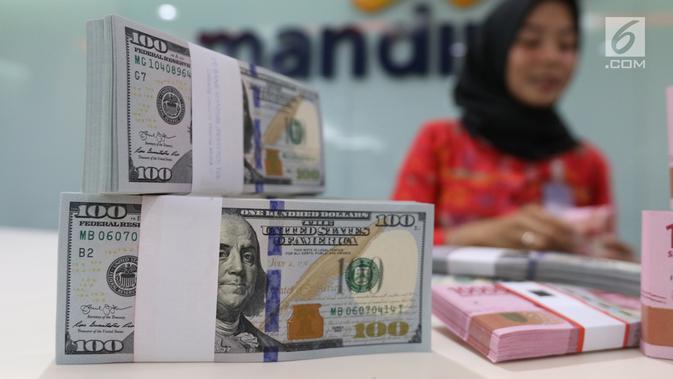 Teller tengah menghitung mata uang rupiah dan dolar di Bank Mandiri, Jakarta, Kamis (10/1). Hingga hari ini, US$ 1 dibanderol Rp 14.020. Rupiah menguat 0,71% dibandingkan posisi penutupan perdagangan hari sebelumnya. (Liputan6.com/Angga Yuniar)