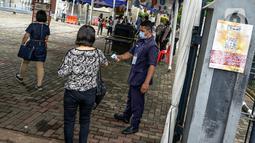 Petugas mengecek suhu tubuh jemaat saat misa Minggu Paskah di Gereja Katedral, Jakarta, Minggu (4/4/2021). Sejumlah personel gabungan TNI-Polri disipakan untuk melakukan pengamanan di sejumlah gereja pada perayaan Paskah. (Liputan6.com/Faizal Fanani)