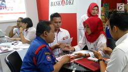 Karyawan Bank DKI menjelaskan aplikasi JakOne Mobile kepada pengunjung Pekan Raya Jakarta di Jakarta (23/5). JakOne Mobile dapat digunakan sebagai alat pembayaran pada merchant yang sudah bekerjasama. (Liputan6.com/Pool/Budi)