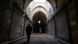 Seorang pria berjalan di lorong di pasar lama di kota tua Aleppo, Suriah (21/1). Kota tua ini meliputi area sekitar 3,5 kilometer persegi dengan lebih dari 120.000 penduduk. (AP Photo / Mstyslav Chernov)