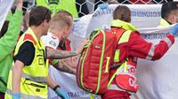 Kapten Timnas Denmark, Simon Kjaer pun sempat menghampiri Eriksen saat dibawa keluar lapangan. Dan Eriksen pun terlihat sudah bisa merespon panggilan Simon Kjaer yang berada disampingnya. (Foto: AFP/Pool/Hannah McKay)