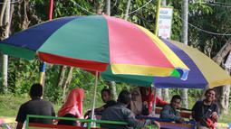 Wisatawan menaiki perahu apung di Wisata Air Toino, Desa Talulobutu, Kecamatan Tapa, Kabupaten Bone Bolango, Gorontalo, Sabtu (30/3). Wisata air yang kian viral di media sosial ini akan semakin ramai pada saat akhir pekan. (Liputan6.com/Arfandi Ibrahim)