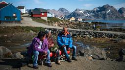 Penduduk mengobrol di Desa Kulusuk, Kota Sermersooq, Greenland, Denmark, 16 Agustus 2019. Sebagian besar penduduk Desa Kulusuk bekerja di sektor pariwisata dan perikanan lokal. (Jonathan NACKSTRAND/AFP)