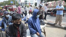 Pengendara yang terjaring razia masker antre untuk didata di Jalan Panjang, Kedoya, Jakarta Barat, Senin (2812/2020). Pengendara yang tidak mengenakan masker langsung menjalani rapid test antigen gratis untuk mencegah penularan COVID-19. (merdeka.com/Dwi Narwoko)