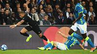 Striker PSG, Kylian Mbappe berusaha melewati pemain Napoli Mario Rui selama pertandingan Grup C Liga Champions di stadion Parc des Princes di Paris, (24/10). PSG bermain imbang 2-2 atas Napoli. (AP Photo / Thibault Camus)