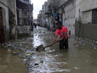 Seorang pria membersihkan jalan yang banjir setelah hujan deras, di Karachi, Pakistan, Selasa (30/7/2019). Departemen Meteorologi Pakistan mengatakan bahwa hujan memasuki provinsi Sindh dari Rajasthan India dan memperkirakan hujan akan turun tiga hari lagi. (AP Photo/Fareed Khan)