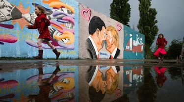 Anak-anak berlari di depan Graffiti yang menggambarkan Presiden AS Trump (kanan) dan Presiden Tiongkok Xi Jinping saling berciuman dengan mengenakan masker di tembok taman umum Mauerpark di Berlin, Jerman, Rabu, (29/4/2020). (AP/Markus Schreiber)