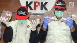 Penyidik KPK menunjukkan barang bukiti uang OTT Bupati Mesuji Khamami senilai Rp 1,2 M di gedung KPK, Jakarta, Kamis (24/1). KPK menetapkan 5 tersangka terkait fee suap proyek infrastruktur di Kabupaten Mesuji. (merdeka.com/Dwi Narwoko)