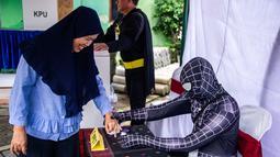 Petugas Kelompok Penyelenggara Pemungutan Suara (KPPS) berkostum superhero Venom membantu warga mencelupkan jari ke tinta dalam Pemilu 2019 di sebuah TPS di Surabaya, Jawa Timur, Rabu (17/4). Petugas KPPS berharap menarik pemilih, khususnya milenial. (Juni Kriswanto/AFP)