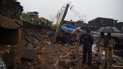 Polisi dan petugas penyelamat mengecek lokasi runtuhnya tembok di Mumbai, India (2/7/2019). Tragedi tersebut terjadi ketika pemukiman pantai yang dipenuhi 20 juta penduduk dihantam hujan lebat selama dua hari berturut-turut, membuat kota terhenti total. (AFP Photo/Punit Paranjpe)
