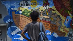 Seorang pria berdiri di depan sebuah mural kampanye pemilu 2019 di Banda Aceh, provinsi Aceh (17/3). Indonesia akan mengadakan pemilihan presiden dan parlemen secara serentak pada 17 April. (AFP Photo/Chaideer Mahyuddin)