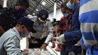 Petugas Dinas Perhubungan mendata para pekerja migran yang baru tiba di terminal Kabupaten Bangkalan. Mereka baru datang dari Malaysia.