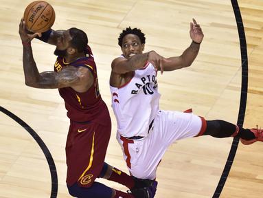 Pemain Cleveland, LeBron James (23) melakukan lay up saat diadang pemain Raptors, DeMar DeRozan (10) pada laga NBA playoffs Eastern Conference semifinal di Air Canada Centre, (1/2/2018). Cavaliers menang 113-112. (Frank Gunn/The Canadian Press via AP)