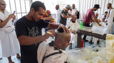 Jemaah haji mencukur rambut kepala atau tahalul usai melaksanakan lempar jumrah, Mina, Arab Saudi, Minggu (11/8/2019). Tahalul termasuk ke dalam serangkaian ibadah haji. (FETHI BELAID/AFP)