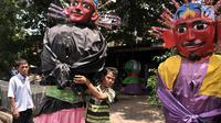 Seorang anak menggendong ondel-ondel saat bersiap untuk mengamen di kawasan Senen, Jakarta, Kamis (27/12). Hanya pengamen ondel-ondel beperalatan lengkap yang diperbolehkan. (Merdeka.com/Iqbal S. Nugroho)