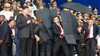 Pengawal melindungi Presiden Venezuela Nicolas Maduro dengan perisai antipeluru saat serangan drone di Caracas, Venezuela, Sabtu (4/8). Serangan terjadi saat Presiden Maduro berpidato dalam HUT ke-81 Tentara Venezuela. (Xinhua via AP)