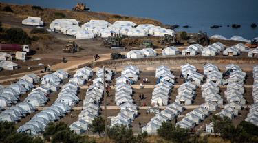 Alat berat beroperasi saat para migran berkumpul di kamp tenda sementara di Kara Tepe, Lesbos, Yunani, Kamis (17/9/2020). Lebih dari 5.000 pencari suaka kehilangan tempat tinggal sepekan setelah kebakaran menghanguskan kamp migran terbesar di Yunani, Kamp Moria. (AP Photo/Panagiotis Balaskas)