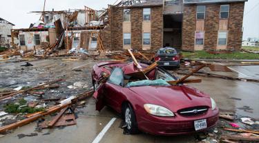 Sebuah mobil hancur tertimpa puing bangunan usai dilanda badai Harvey di Rockport, Texas (26/8). Akibat badai tersebut, Wali Kota Rockport Charles Wax mengungkapkan bahwa satu orang ditemukan meninggal. (Courtney Sacco/Corpus Christi Caller-Times via AP)