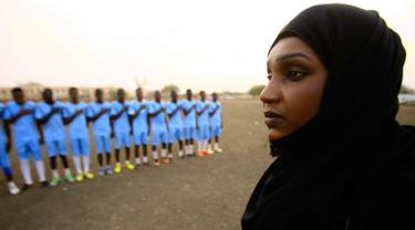 Salma al-Majidi melihat para pemain klub Al-Ahly Al-Gadaref selama sesi pelatihan di kota Gedaref, timur Khartoum (17/2). Salma diakui FIFA sebagai wanita Arab dan Sudan pertama yang melatih tim sepak bola pria Arab. (AFP Photo/Ashraf Shazly)