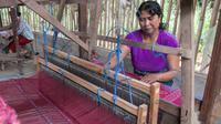 Ibu Kadek Sami beserta perempuan Kolok lainnya fokus di atas mesin tenun membuat motif kuda laut ciri khas Pertamina.
