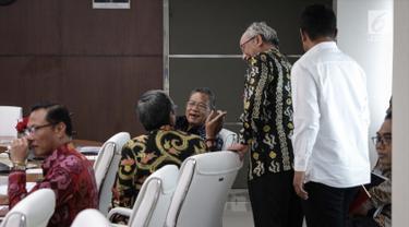 Menko Perekonomian Darmin Nasution berbincang saat mengunggu Rakor Tingkat Menteri di Kantor Kemenko PMK, Jakarta, Rabu (6/11). Rakor tersebut membahas tentang Evaluasi Pelaksanaan Program Rastra dan BPNT tahun 2017. (Liputan6.com/Faizal Fanani)