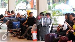 Sejumlah calon penumpang duduk menanti waktu masuk ke dalam Bandara Halim Perdanakusuma Jakarta, Senin (4/7). H-2 jelang Idul Fitri 1437 H, ribuan calon penumpang diberangkatkan dari Bandara Halim Perdanakusuma. (Liputan6.com/Helmi Fithriansyah)