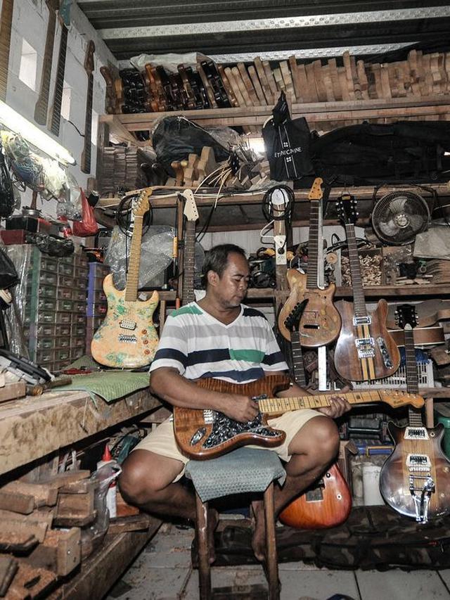 Bone bermain gitar di sela merawat ternak ikan cupang hias di workshop Bone's Costum Guitar, Jakarta, Rabu (10/3/2021). Untuk mencukupi kebutuhan sehari-hari, ayah dari 4 anak ini mencari sampingan dengan membuka ternak cupang hias sembari menunggu pelanggan gitar. (merdeka.com/Iqbal S Nugroho)