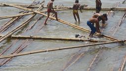 Anak-anak bermain air di atas batang kayu bekas dermaga sandar kapal tradisional di Kawasan Cilincing, Jakarta, Selasa (10/4). Aktifitas bermain laut di pesisir pantai teluk Jakarta ini menjadi keseharian mereka sepeluang sekolah.(Merdeka.com/Imam Buhori)