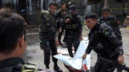 Polisi mengevakuasi kantong jenazah pasca ledakan bom di Gereja Katolik Jolo, Filipina Selatan, Minggu (27/1). Ledakan pertama terjadi tepat ketika Misa Minggu berlangsung, sekitar pukul 08.45 waktu setempat.(Nickee Butlangan/AFP)