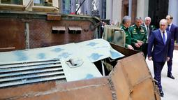 Presiden Vladimir Putin melihat kendaraan tempur saat mengunjungi pameran di markas militer Rusia di Moskow (30/1). Kunjungan Putin sebagai bagian dari sebuah konferensi mengenai kampanye Rusia di Suriah. (Mikhail Klimentyev, Sputnik, Kremlin Pool/AP)