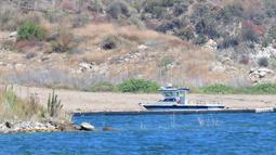 Sebuah kapal sheriff Ventura County terlihat di dekat teluk kecil di Danau Piru, California, Senin (13/7/2020). Jasad aktris Glee Naya Rivera yang dinyatakan menghilang pada 8 Juni 2020 lalu telah ditemukan tewas di Danau Piru pada Senin (13/7). (Frederic J. BROWN / AFP)