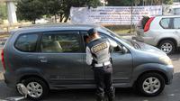 Petugas Dishub DKI membagikan selebaran untuk mensosialisasikan perluasan ganjil genap di kawasan Tomang, Jakarta, Senin (2/7). Hari ini merupakan hari pertama uji coba yang digelar jelang pelaksanaan Asian Games 2018. (Liputan6.com/Arya Manggala)