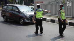 Petugas Kepolisian memberhentikan mobil berplat nomor genap yang memasuki persimpangan Jalan Dharmawangsa X dan Jalan Fatmawati, Jakarta, Senin (9/9/2019). Polisi mulai menindak pengendara yang melanggar perluasan ganjil genap di Jakarta Selatan. (Liputan6.com/Immanuel Antonius)