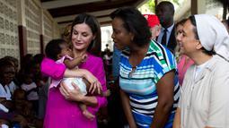 Ratu Spanyol Letizia menggendong seorang bayi perempuan dalam kunjungannya ke rumah sakit di daerah kumuh Soleil, Haiti, 23 Mei 2018. Ini merupakan kunjungan pertama Ratu Letizia ke negara termiskin di benua Amerika tersebut. (AP/Dieu Nalio Chery)