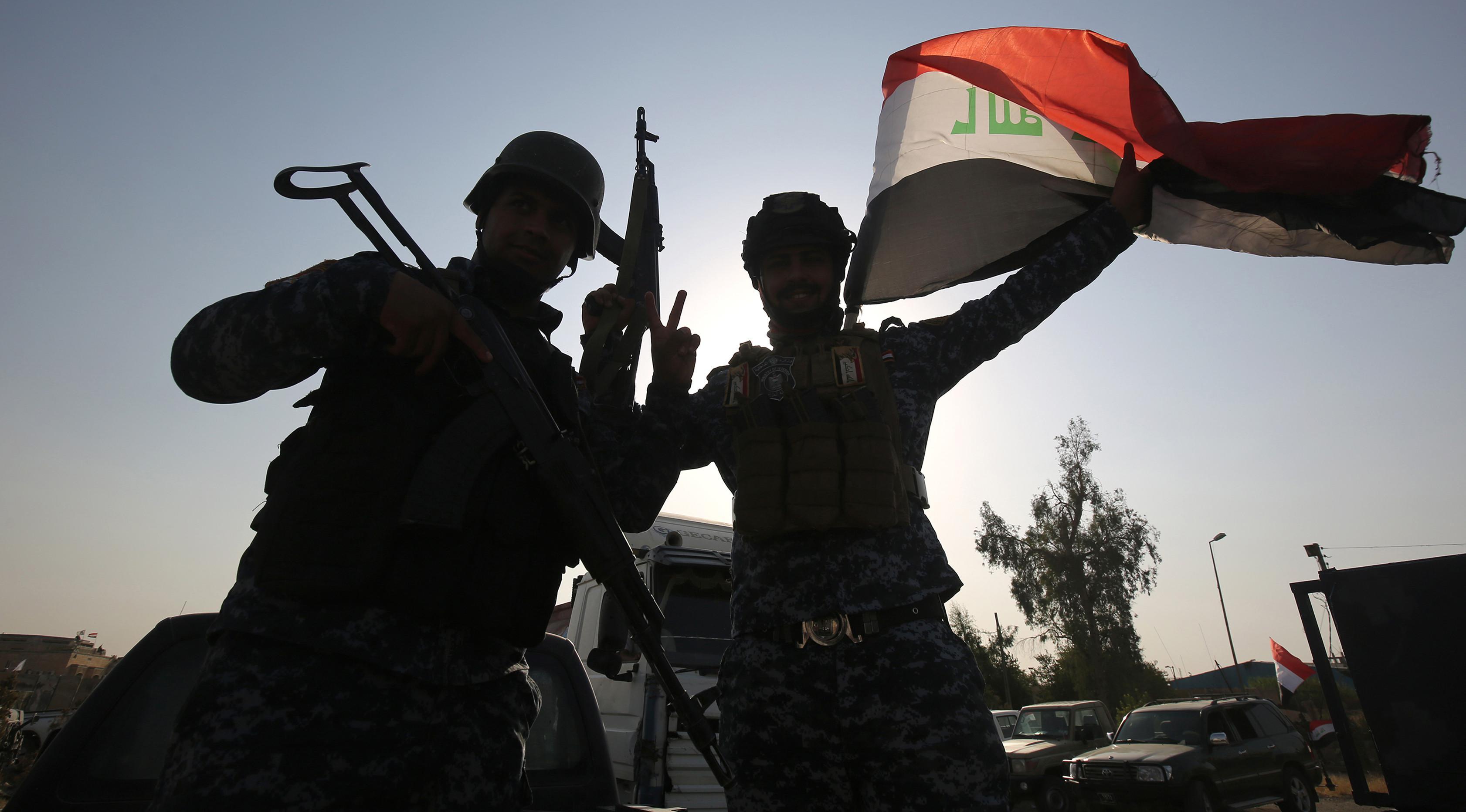 Anggota polisi Federal mengibarkan bendera nasional Irak saat merayakan keberhasilan mereka menyingkirkan militan ISIS dari Kota Tua Mosul, Minggu (9/7). ISIS merebut Mosul pada musim panas 2014. (AHMAD AL-RUBAYE/AFP)