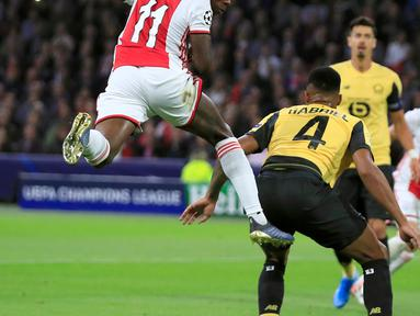 Pemain Ajax, Quincy Promes (kiri) mencetak gol lewat sundulan ke gawang Lille yang dijaga kiper Mike Maignan (kanan) pada laga Grup H Liga Champions di Amsterdam, Belanda, Selasa (17/9/2019). Ajax memuncaki klasemen Grup H Liga Champions usai mengalahkan Lille 3-0. (AP Photo/Peter Dejong)