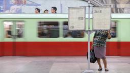 Seorang komuter membaca koran pada platform stasiun kereta bawah tanah atau metro Pyongyang, 6 September 2018. Di stasiun kereta bawah tanah ini tidak terlihatnya iklan laiknya stasiun pada umumnya. (AFP / Ed JONES)