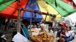 Warga membeli gorengan di di kawasan Kota Tua, Jakarta Selasa (2/1). Meski ada larangan berdagang di kawasan tersebut, pedagang tetap nekat berjualan. (Liputan6.com/Johan Tallo)