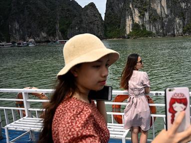 Wisatawan domestik berpose untuk foto di atas kapal di tengah Ha Long Bay, Quang Ninh, Vietnam, (16/5/2020). Sempat terpukul akibat pandemi virus corona Covid-19, pariwisata Vietnam kembali menggeliat setelah otoritas setempat melonggarkan pembatasan perjalanan. (AFP/Manan Vatsyayana)
