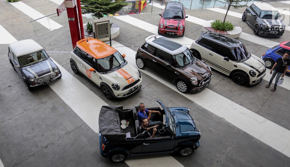 Presiden Director BMW Group, Ramesh Divyanatha dan Co Founder Indonesia Coopret Registry, Peter Anugrah menaiki mobil mini klasik pada Indonesia Mini Day 2018 di QBig BSD, Tangerang, Sabtu (15/12). (Liputan6.com/Fery Pradolo)