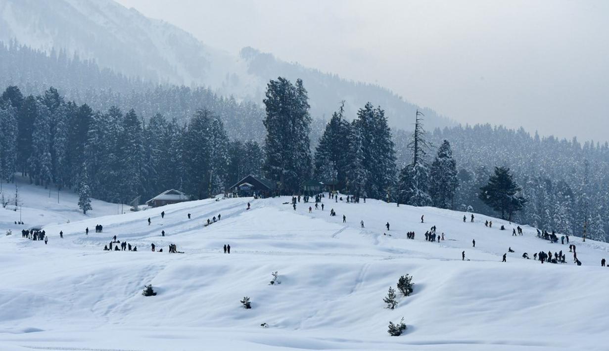 Suasana saat para wisatawan mengunjungi resor ski di Gulmarg, sekitar 55 km utara Srinagar, Jammu dan Kashmir, India, 25 Januari 2021. Gulmarg merupakan destinasi wisata salju di Jammu dan Kashmir. (Tauseef MUSTAFA/AFP)