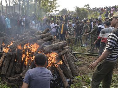 Polisi dan pekerja kehutanan bersama penduduk desa menyaksikan tubuh gajah dibakar setelah kereta penumpang melaju menabrak dua gajah yang melintasi rel di desa Batasi dekat perbatasan India-Nepal, sekitar 37 km dari Siliguri (11/12/2019). (AFP/Diptendu Dutta)