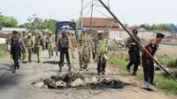 Satpol PP dan polisi membersihkan material batang bambu dan batu yang digunakan warga untuk memblokade jalan rusak akibat proyek tol Pemalang. (Foto: Liputan6.com/Polres Pemalang/Muhamad Ridlo)