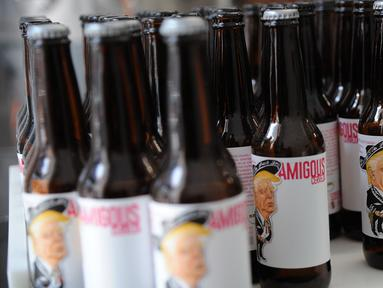 Sejumlah botol bir bergambar Presiden AS, Donald Trump di kemas di perusaahan Cru Cru Brewery di Mexico City (15/6). Botol bir ini labelnya bergambar Donald Trump dengan mengenakan pakaian bergaya Mariachi.  (AFP Photo/Bernardo Montoya)