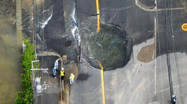 Air keluar dari retakan dan membanjiri jalan menyusul gempa bumi di Takatsuki, Osaka, Jepang, Senin (18/6). Gempa berkekuatan 6,1 SR menghantam Osaka pada Senin pagi. (Yohei/Nishimura/Kyodo News via AP)