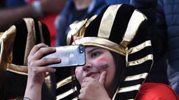 Seorang suporter Mesir selfie saat akan menonton laga Grup A Piala Dunia melawan Uruguay di Stadion Ekaterinburg, Yekaterinburg, Jumat (15/6/2018). Terakhir kali Mesir lolos ke Piala Dunia tahun 1990. (AFP/Anne-Christine Poujoulat)
